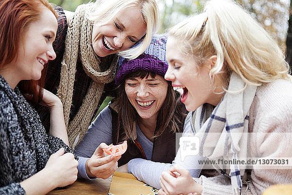 Glückliche Freunde  die bei Tisch lachen