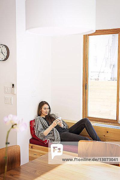 Frau benutzt Mobiltelefon  während sie zu Hause auf dem Sofa liegt