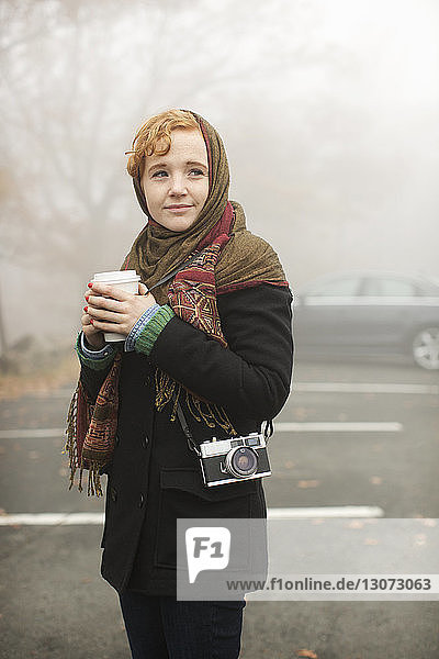 Woman with disposable cup looking away while standing on road in forest