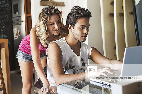 Couple looking at laptop computer in living room at home