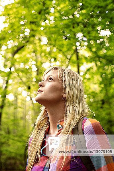 Nachdenkliche Frau schaut auf  während sie im Wald steht