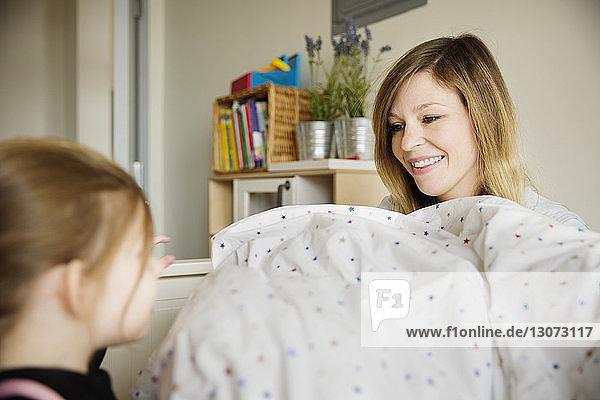 Glückliche Mutter sieht Tochter zu Hause an