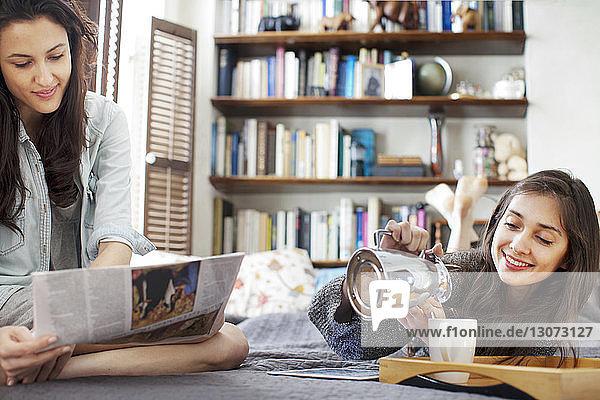 Frau liest Zeitung  während Schwester Kaffee in Tasse gießt