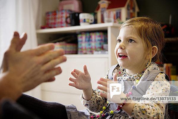 Glückliches Mädchen spielt zu Hause mit dem Vater
