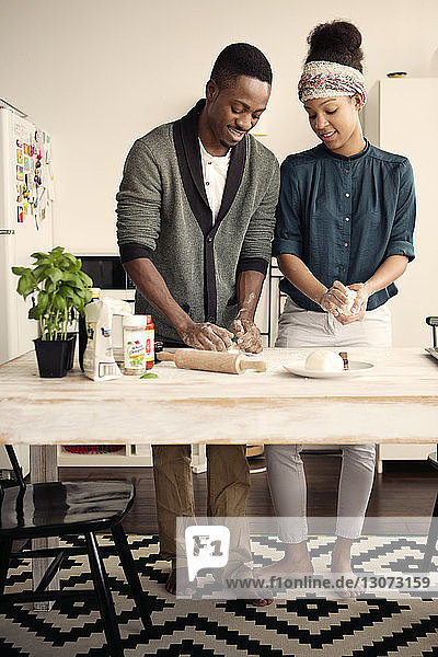 Lächelndes Paar in voller Länge beim Teigkneten am Küchentisch