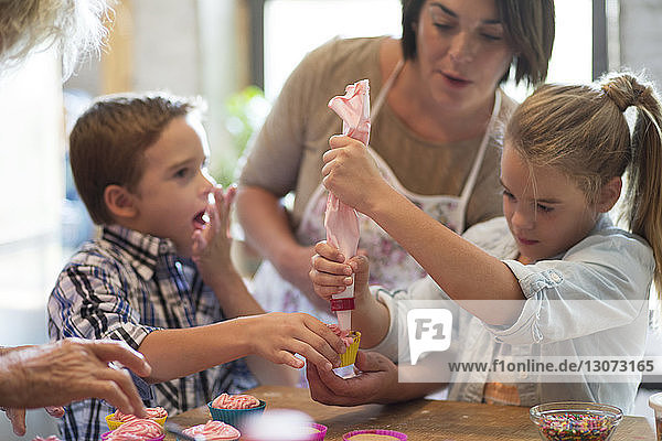 Family making cupcakes in kitchen