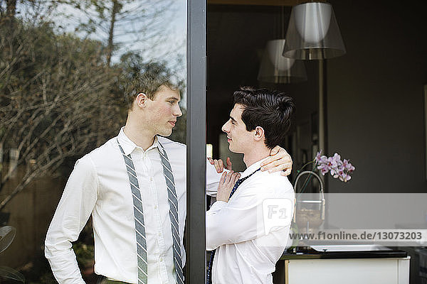 Affectionate gay couple standing at doorway