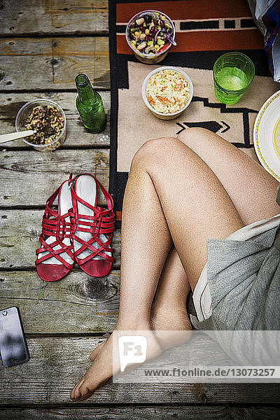 Low section of woman sitting on wooden porch