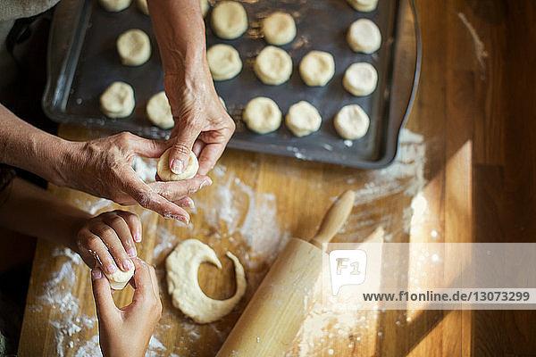 Ausgeschnittenes Bild von Enkelin und Großmutter  die an der Küchentheke Kekse backen