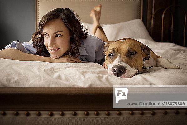 Frau schaut weg  während sie sich zu Hause mit Hund im Bett entspannt