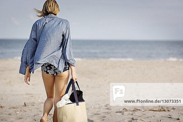 Rückansicht einer Frau  die am Strand auf Sand läuft