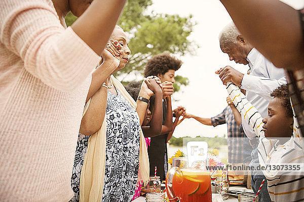 Familie betet vor dem Mittagessen  während sie im Hinterhof am Tisch steht