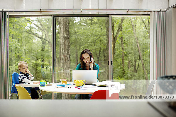 Lächelnde Mutter mit Technik sitzt neben dem Sohn am Tisch am Fenster
