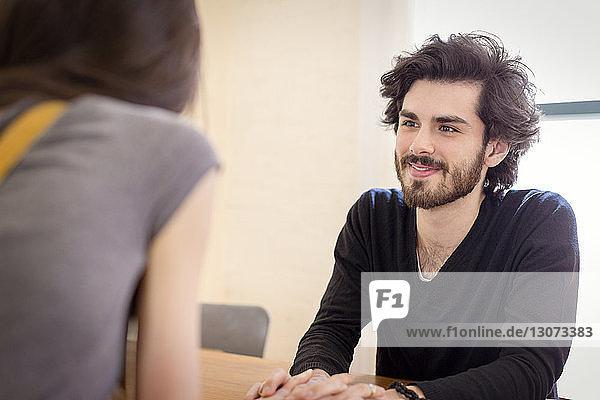 Lächelnder Mann hält Hände einer Frau  während er zu Hause am Tisch sitzt
