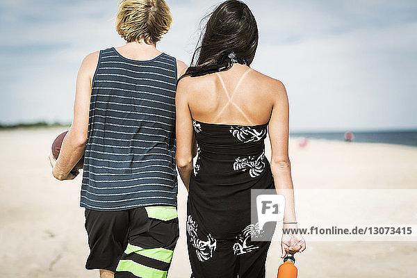 Rückansicht eines Paares  das am Strand auf Sand läuft