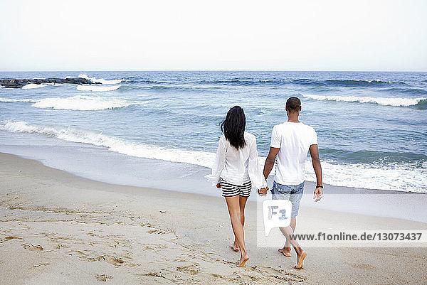 Rückansicht eines Paares  das sich beim Strandspaziergang am Ufer an den Händen hält