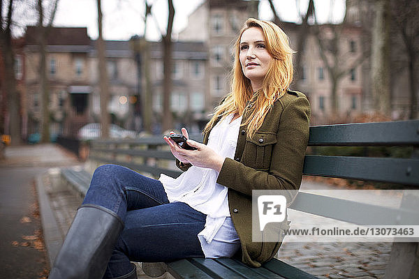 Woman looking away while holding mobile phone on bench