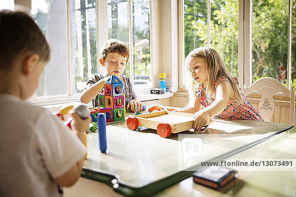 Siblings playing with toy blocks at home