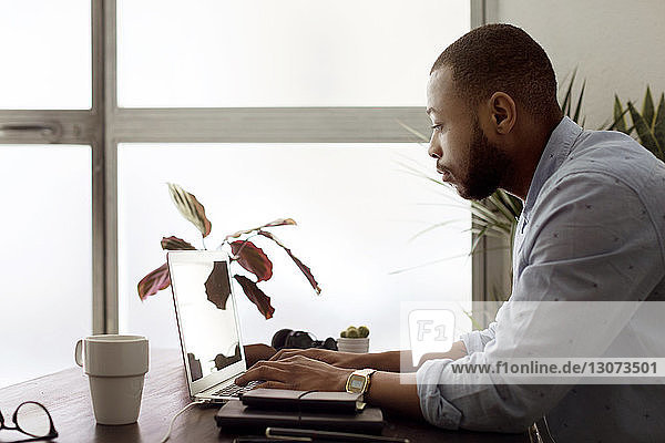 Side view of businessman using laptop at desk in creative office