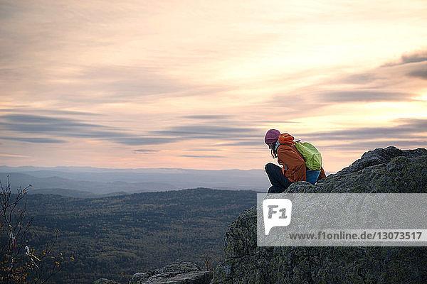 Frau sitzt auf Berg gegen bewölkten Himmel bei Sonnenuntergang