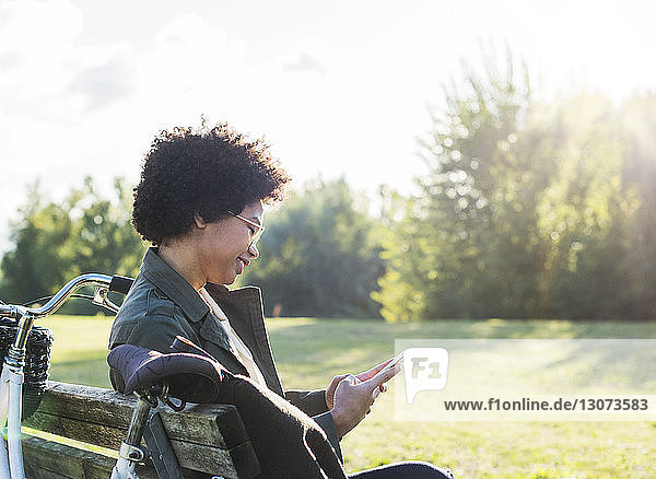 Smiling woman using phone while sitting on bench at park during sunny day