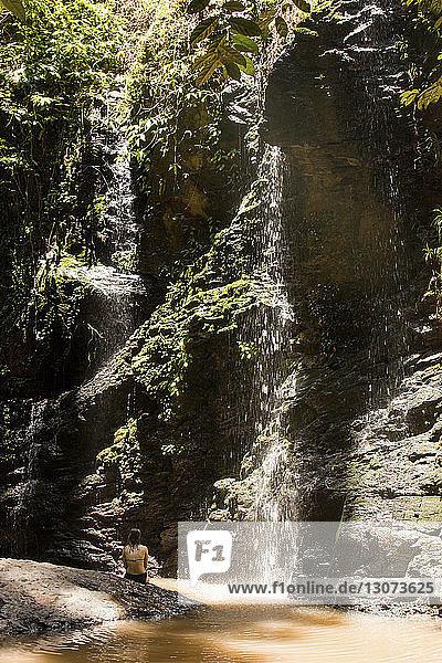 Rückansicht einer Frau  die am Wasserfall im Wald sitzt