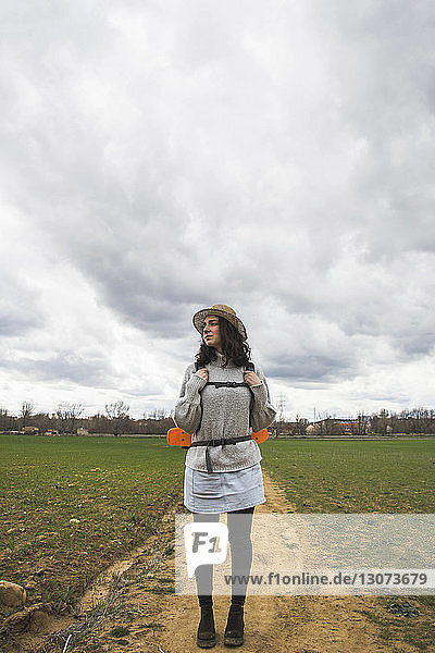 Full length of young woman standing on field against cloudy sky