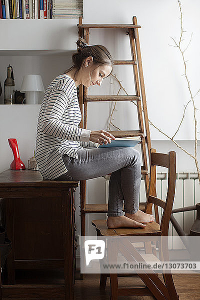 Woman reading book while sitting on wooden table at home