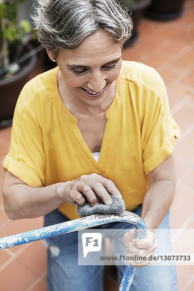 High angle view of happy woman scrubbing metallic chair at yard