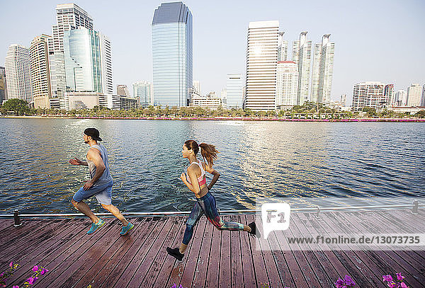 Man and woman running on wooden walkway by river against buildings