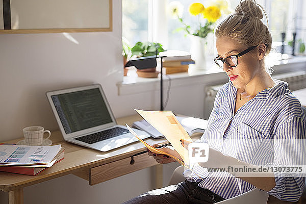 Woman reading paper while sitting on chair