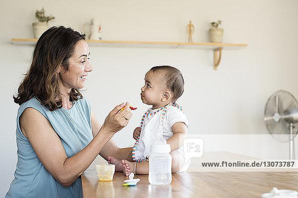 Mutter füttert Säugling zu Hause am Tisch sitzend