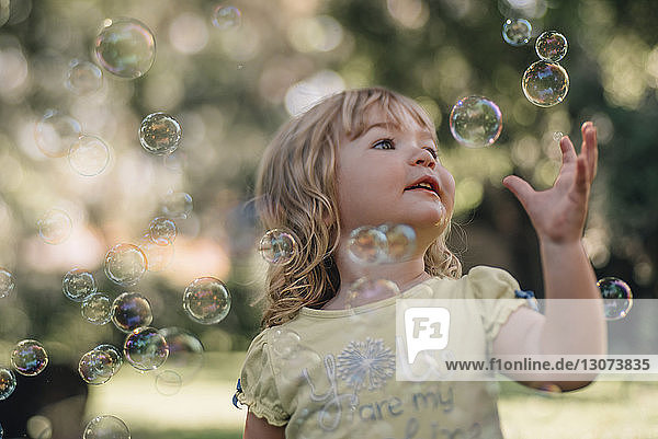 Cute baby girl reaching for bubbles flying in air at park