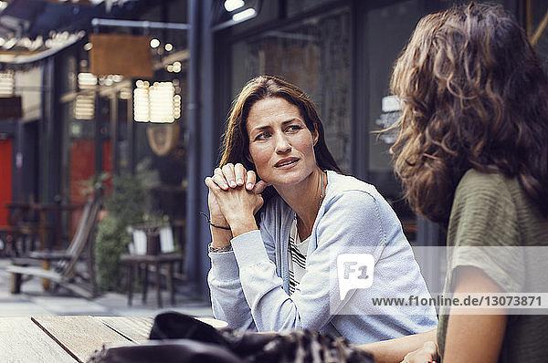 Reife Frau unterhält sich mit Freundin im Straßencafé