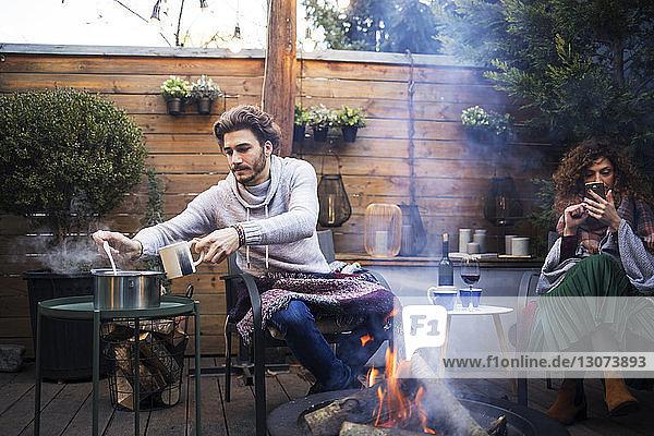 Mann nimmt Nahrung zu sich  während eine Freundin an einer Feuergrube im Hinterhof ein Handy benutzt