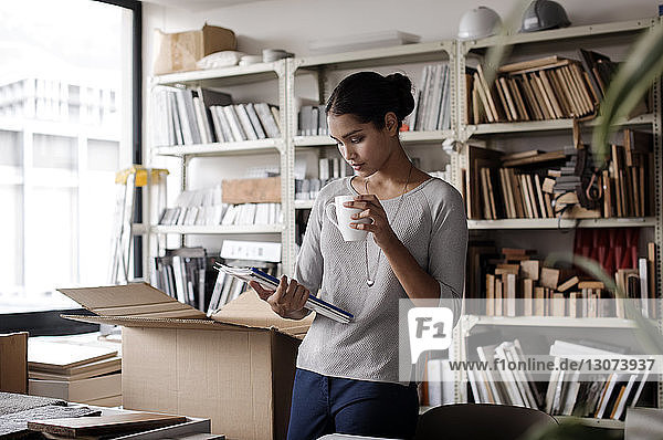 Interior designer holding coffee mug while examining files in office