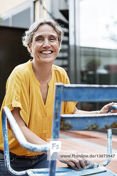 Portrait of cheerful mature woman scrubbing metallic chair with steel wool at yard