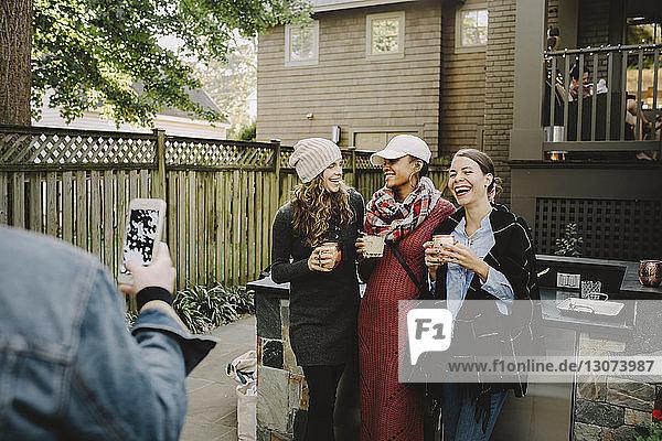 Mann fotografiert Freunde  die Getränke halten  während sie im Hinterhof stehen