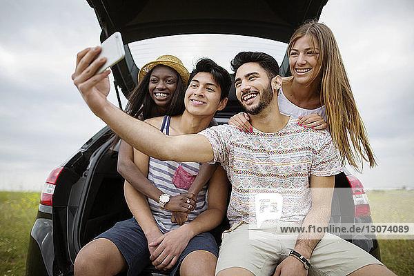 Glückliche multiethnische Freunde  die sich im Kofferraum eines Autos auf dem Spielfeld sitzend per Smartphone selbstständig machen