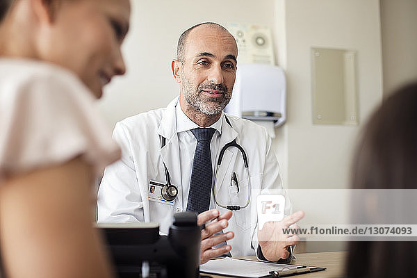 Doctor smiling while talking to patient with mother in hospital