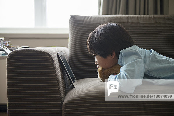 Side view of boy looking at tablet while lying on sofa at home