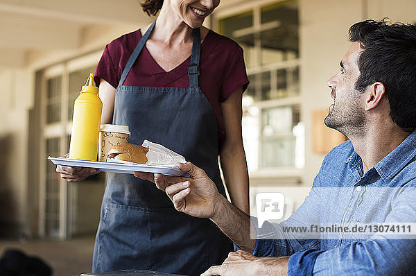 Female owner serving food for customer sitting at table