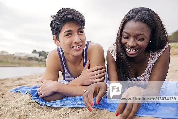 Glückliches multiethnisches Paar liegt auf einer Decke am Strand