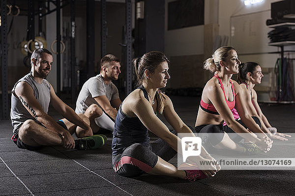 Male and female athletes doing short adductor exercise in gym