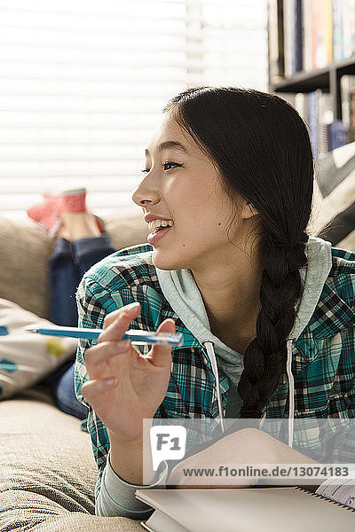 Lächelndes Teenager-Mädchen schaut weg  während es zu Hause auf der Couch Hausaufgaben macht