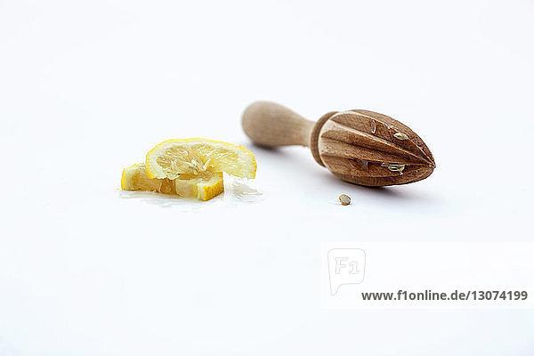 Zitronenscheiben mit hölzerner Reibahle auf weißem Hintergrund