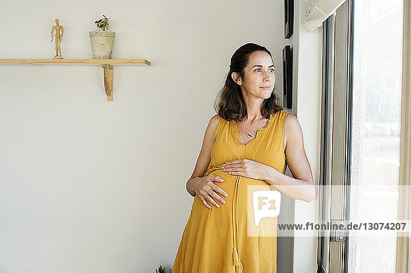 Nachdenkliche schwangere Frau steht zu Hause am Fenster