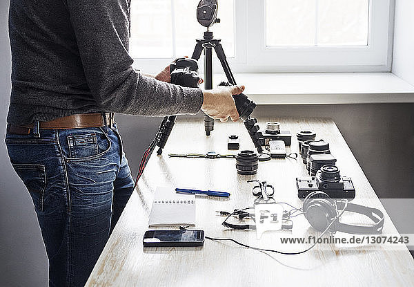 Midsection of male photographer holding lens and camera by table