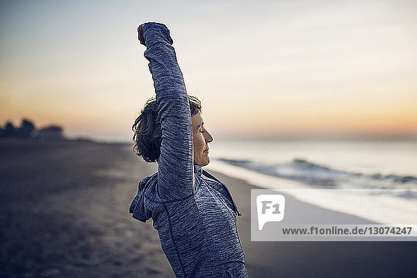 Side view of woman stretching at beach against sky