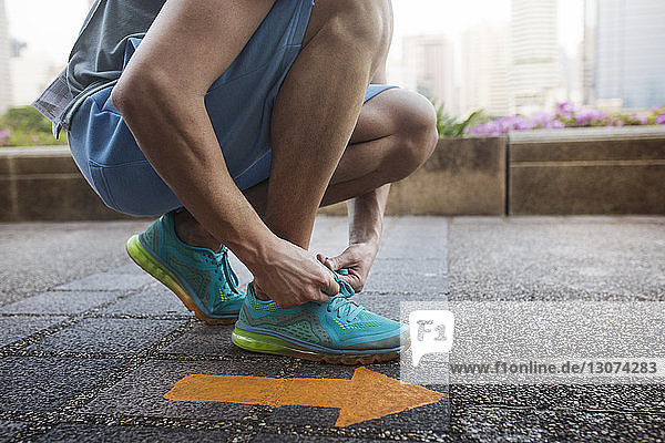 Low section of man tying shoe lace while kneeling by arrow symbol on floor